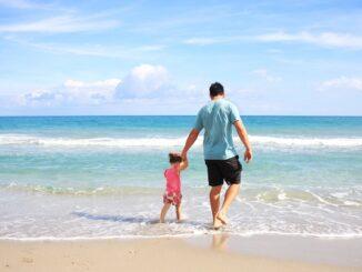 Far og datter er på ferie på strand