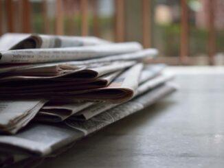Stak af aviser på bord